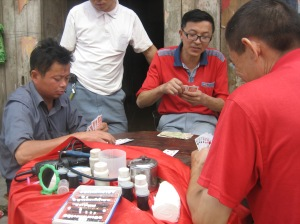 A group of men playing cards in Zhouhe 周河--one of them has pushed aside his tabletop display of equipment for selling false teeth to make room for the game